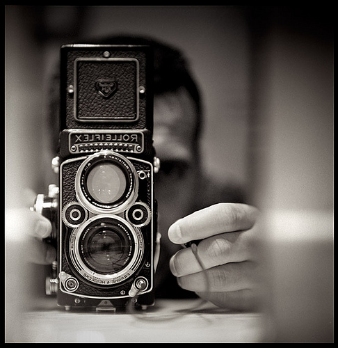 Old school camera with a man behind ready to take a picture