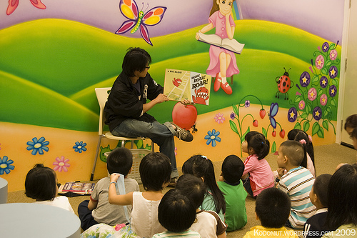 A teacher in front of young students telling them a story from a picture book.