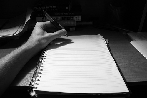 A left hand holding a pen starting to write on a blank piece of paper.