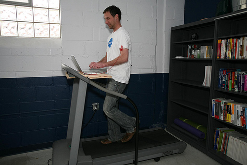 A man working on a laptop while walking on a treadmill, with bookshelves in the background.